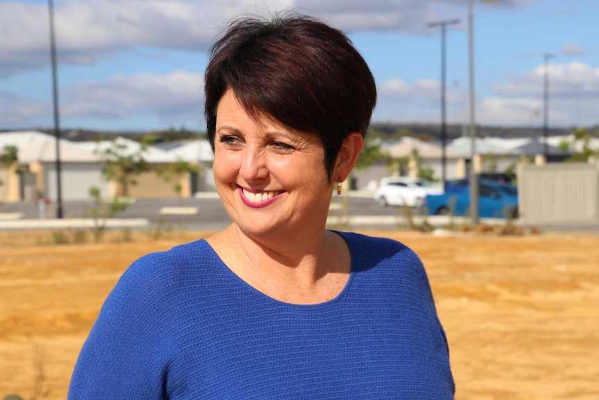 A smiling Alyssa Hayden stands outdoors in front of a housing estate wearing a blue top.