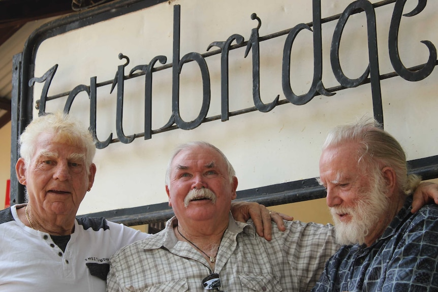 "A group of men stand in front of a sign that says ""Fairbridge"""