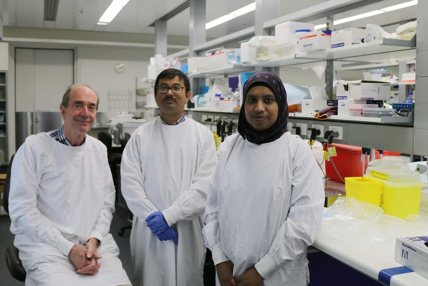 Professor Roger Smith sits in a lab with his colleagues Kaushik Maiti and Zakia Sultana
