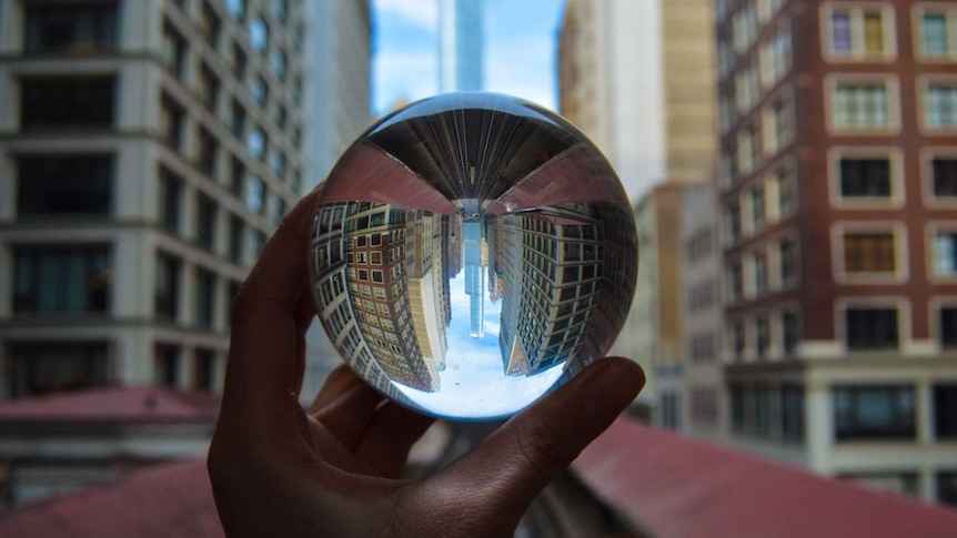 hand holding small crystal ball up with skyscrapers in the background
