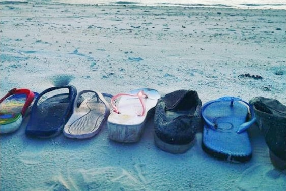 A line of unpaired thongs or flip flops laying at the waters edge in what looks like an exotic location