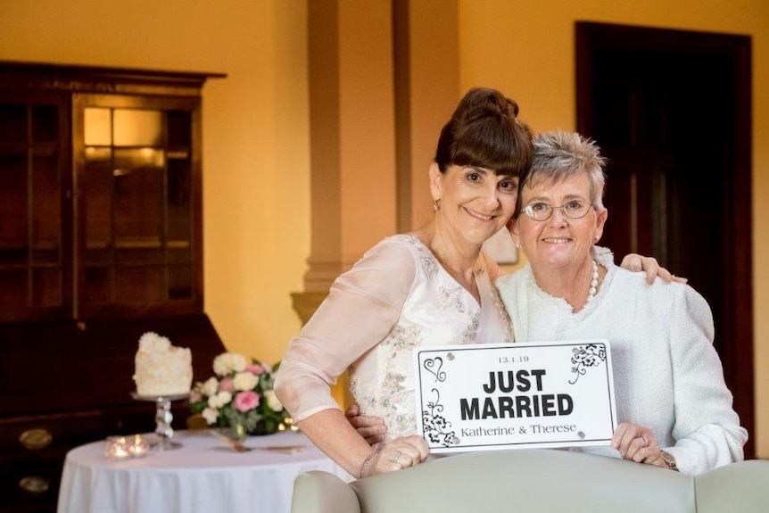 Two women wearing white and holding a 'just married' sign.