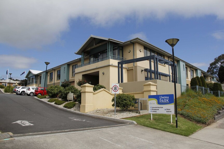 """An off-white building on a sloping street with a sign out the front saying """"Umina Park""""."""