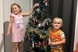 Two young kids stand in front of a Christmas tree