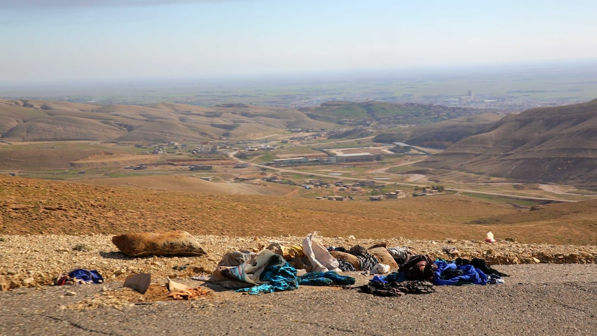 Yazidi clothes lay scattered on the road overlooking Sinjar were thousands fled IS forces