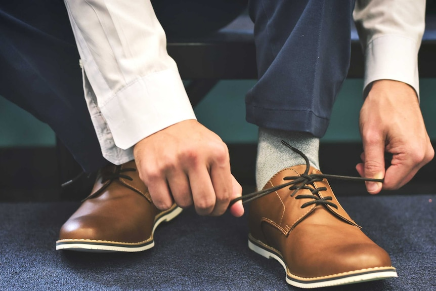 A man ties laces on a pair of brown leather shoes to depict a basic item from a men's workwear wardrobe.