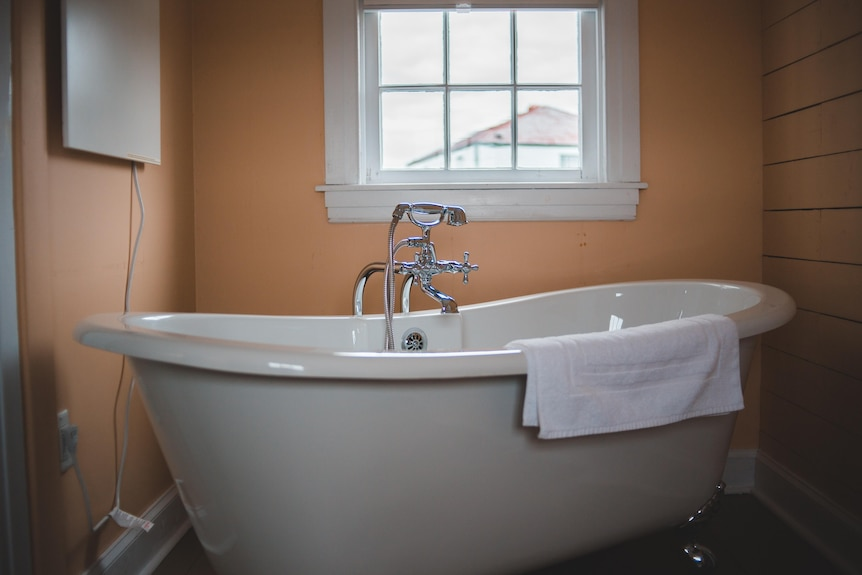 A decadent freestanding bath with is seen with a silver tap and showerhead in a yellow-orange room with a window above it.
