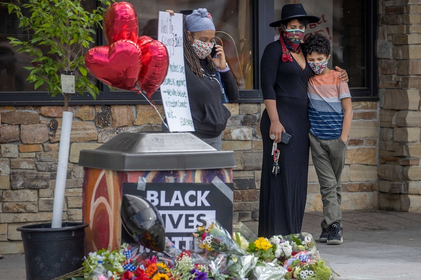 A mother holds her son close as she stood to pay respect at a memorial on the street side.
