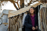 Ronnie Eagles stands outside her caravan near where her home once stood.