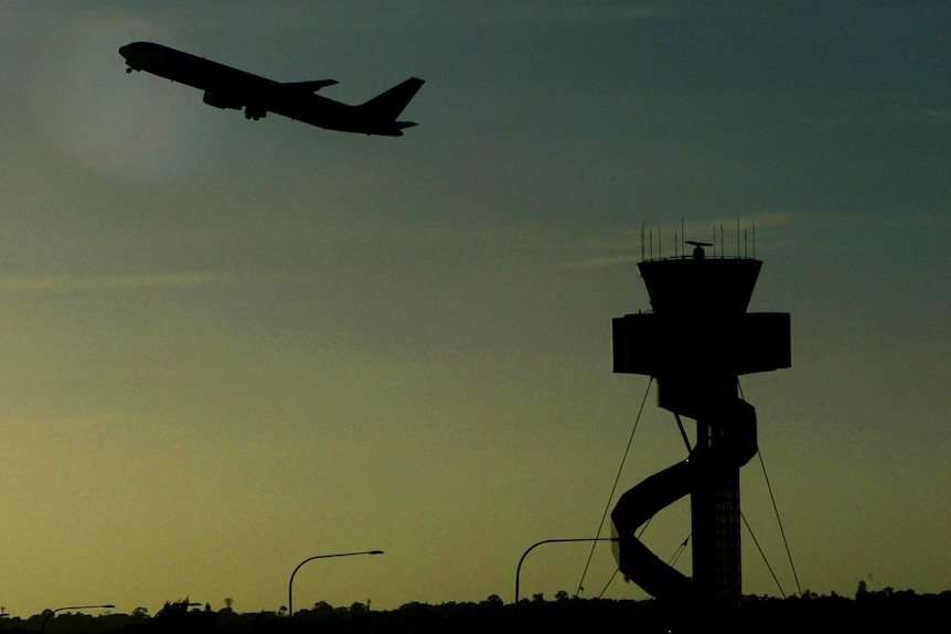 Passenger plane and air traffic control tower at Sydney airport