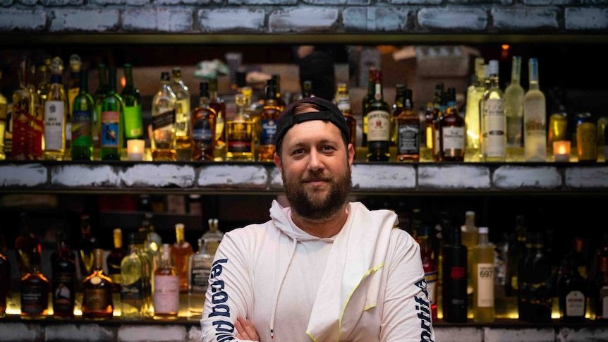 A man in a cap against a stocked bar