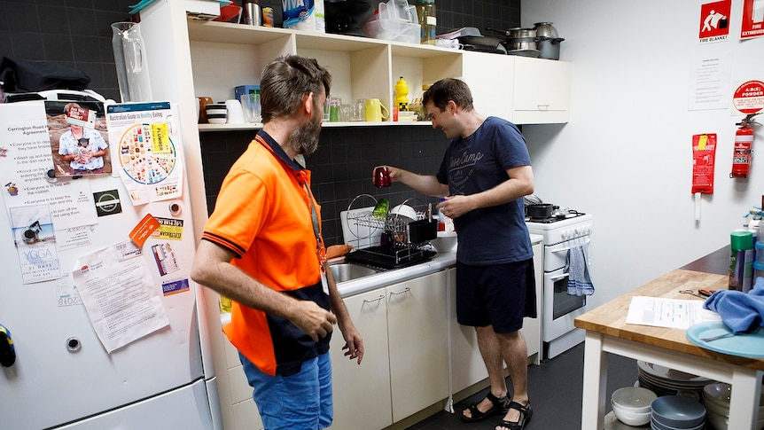 A man puts away cups from a kitchen drainer while another man watches for a story on share housing.