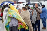 People wrapped in blankets wait in line to fill propane tanks