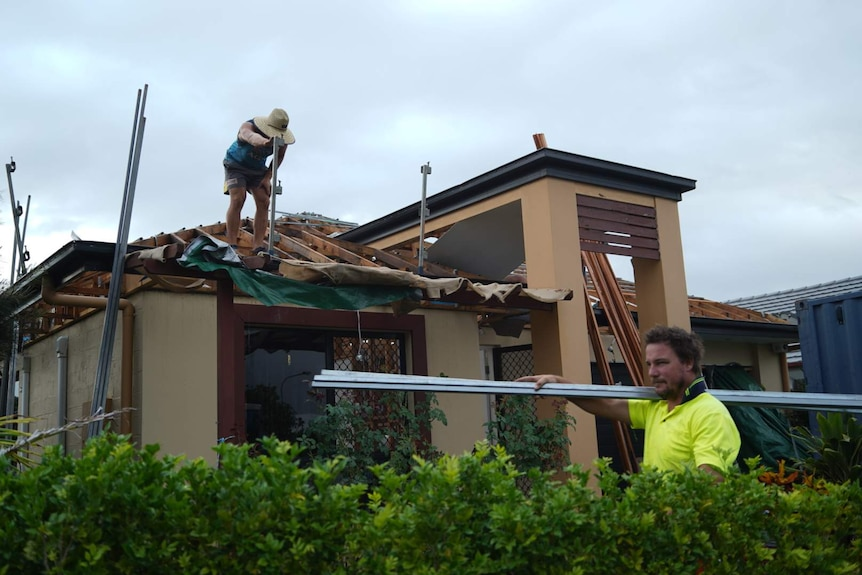 Roofers stand on top of the damaged roof of a house.