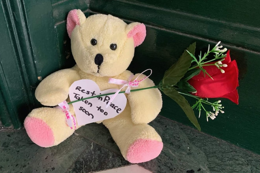 a teddy bear holding a rose with a note reading rest in peace taken too soon