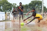 A grou of kids dive for a football in a puddle on the Tiwi Islands.