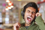 A man is singing his heart out with headphones on.