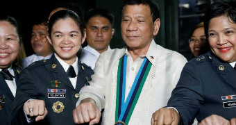 Duterte fist bumps with female military officers in the Philippines