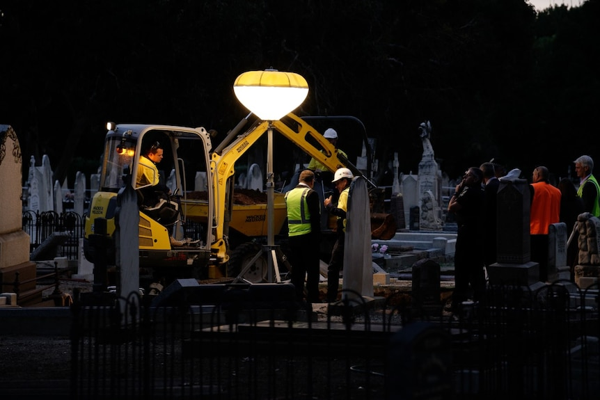 An excavator and several workers stand around a grave lit with a bright light