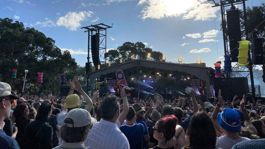 A crowd gathers in front of a stage at a music festival on a sunny day
