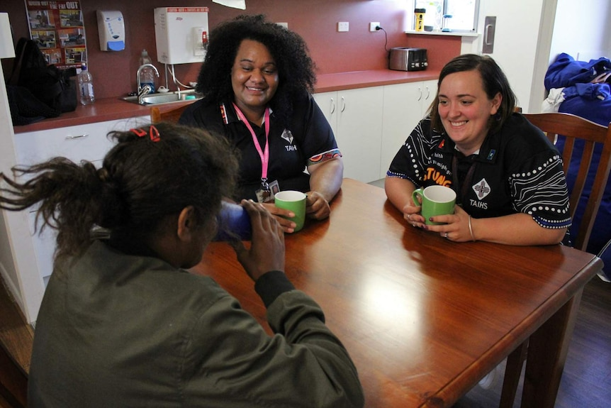 Two women sit at a table speaking with a young Indigenous woman.