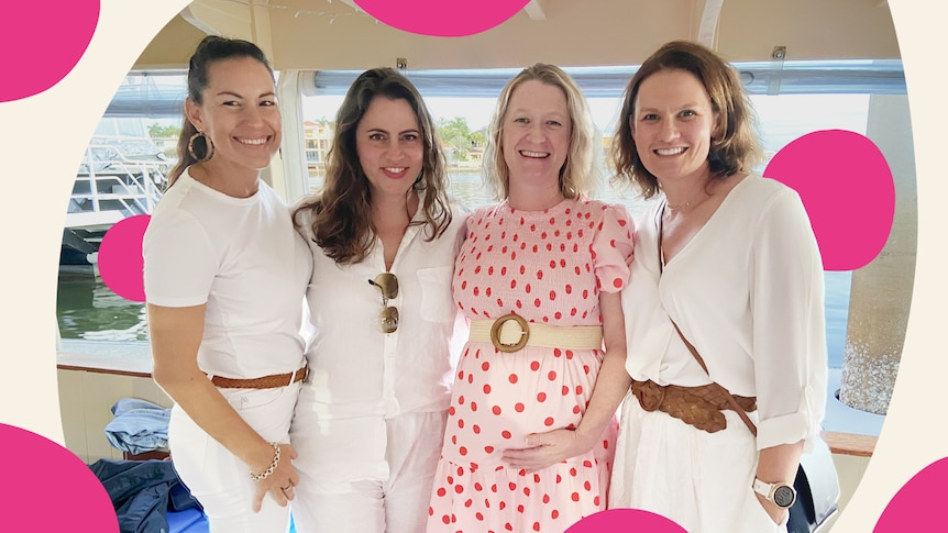 A pregnant woman in a pink dress surrounded by her friends.