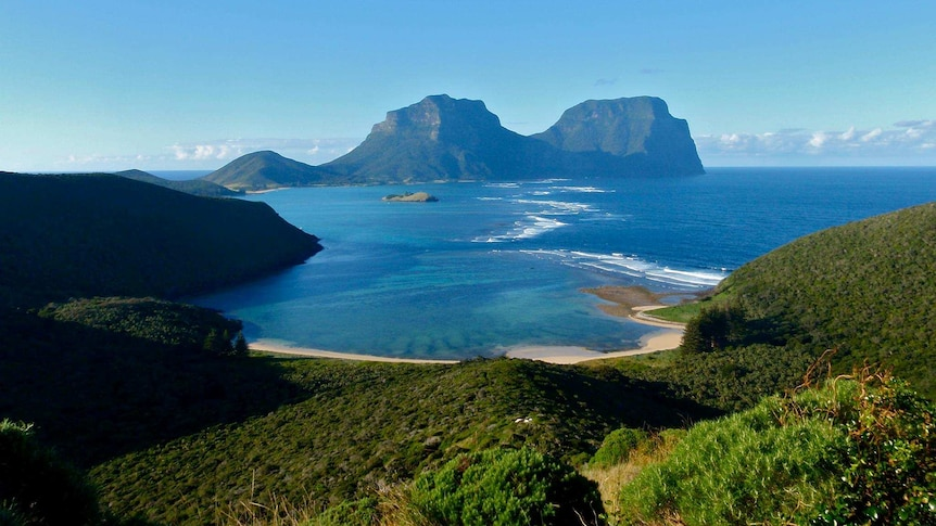Lord Howe Island with beach in the foreground and rocky outcrops in the background