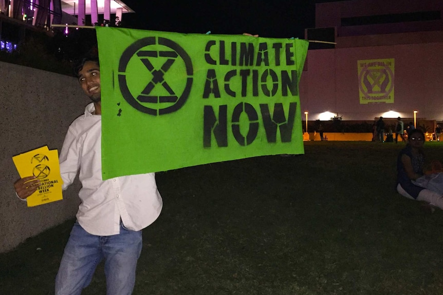 "Extinction Rebellion protester with a sign saying ""Climate Action Now"" near QPAC in Brisbane"