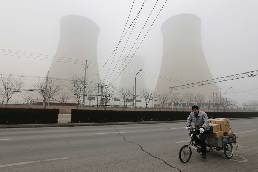 A man cycles past the water-cooling towers of a coal-fired power plant on a hazy day in Beijing.