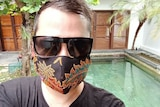 A man with brown hair wearing black sunglasses and a black mask with a colourful flower pattern stand in front of a pool.