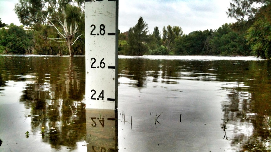 The Queanbeyan River laps at a water level marker.
