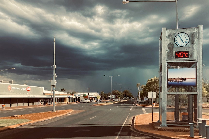 Dark rain clouds over the empty main street a clock by the side of the road says the temperature is 40 degrees celsius.