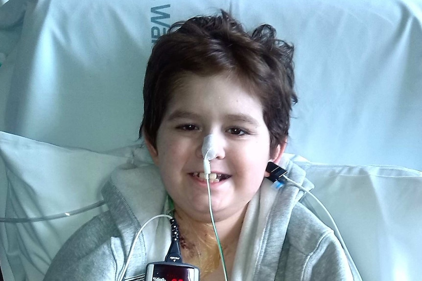 Sean Rice sitting in hospital bed smiling after surgery
