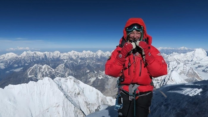 Woman in red jacket stands on mount Everest with snowy peaks below