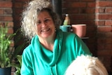 A woman laughs while holding her dog