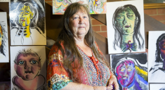 Di stands surrounded by her drawings that representing parts of herself