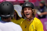 An Australian skateboarder stands wide-eyed with a huge smile as he leads the Olympic men's park competition.