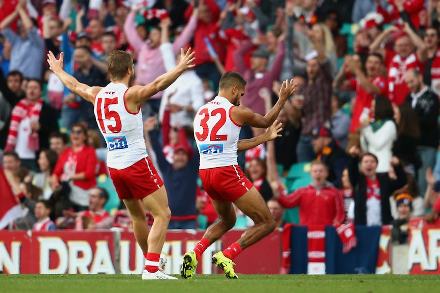 Lewis Jetta celebrates a goal in support of team-mate Adam Goodes