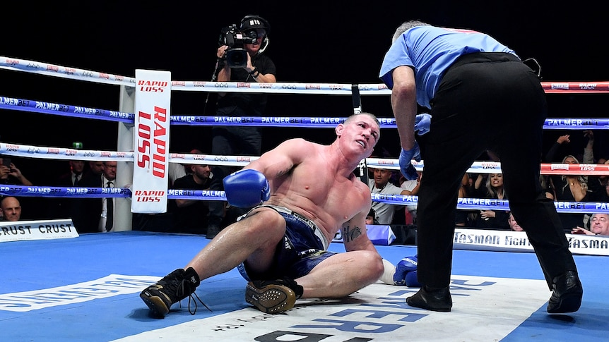Paul gallen looks up at a referee as he lies in a boxing ring, who is bending over him and pointing at him