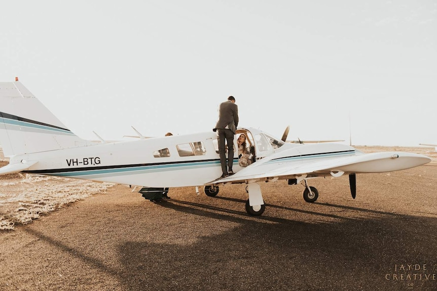 A woman in a wedding dress sits inside a small plane as a man in a suit helps her out the side door.