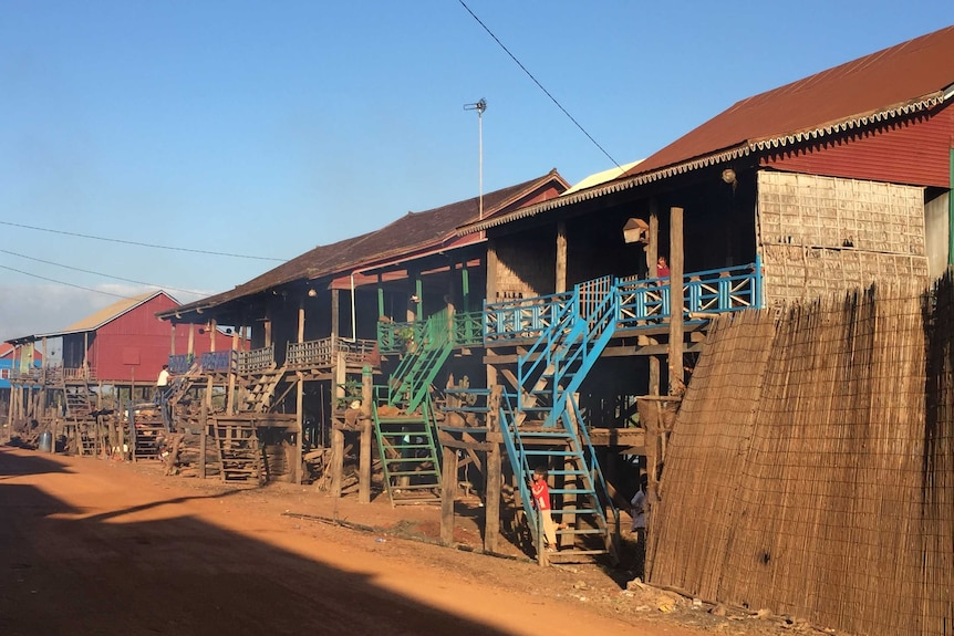 A series of houses on stilts sit above a dusty street