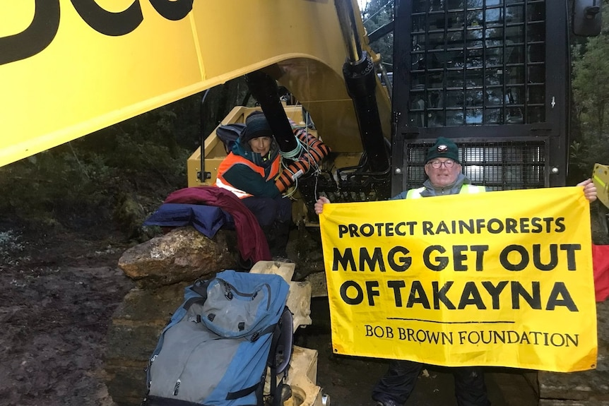 Two people sit on machinery, one holding a sign saying MMG Get out of Takayna.