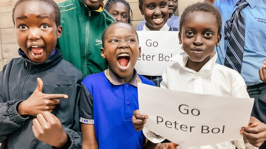 a group of students in uniform hold up a 'go peter bol' sign