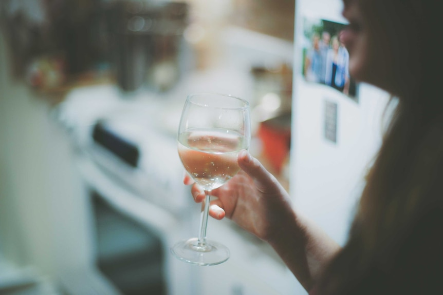 Woman holds a wine glass full of water