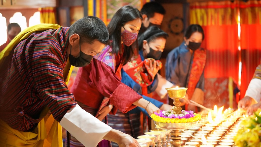 A row of Bhutanese people lighting candles