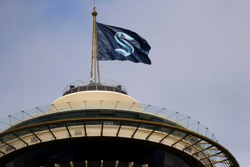 A flag with the logo of a new ice hockey franchise flaps in the wind on top of a Seattle landmark.