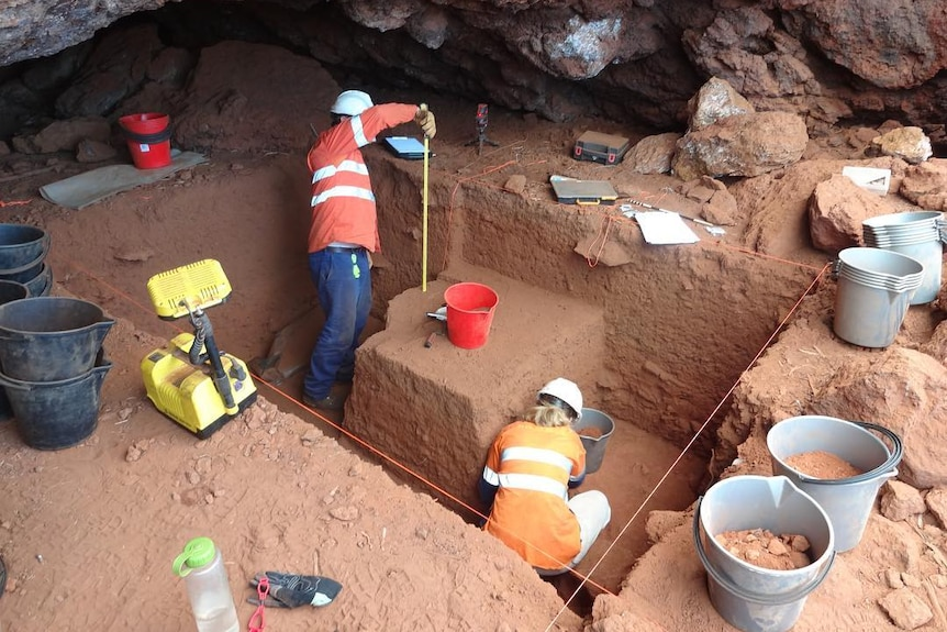 people in a cave measuring and digging