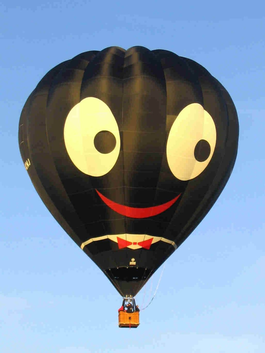 A black balloon depicting a face with wide white eyes and bright red lips.