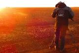 Cameraman filming sunset in rural area.