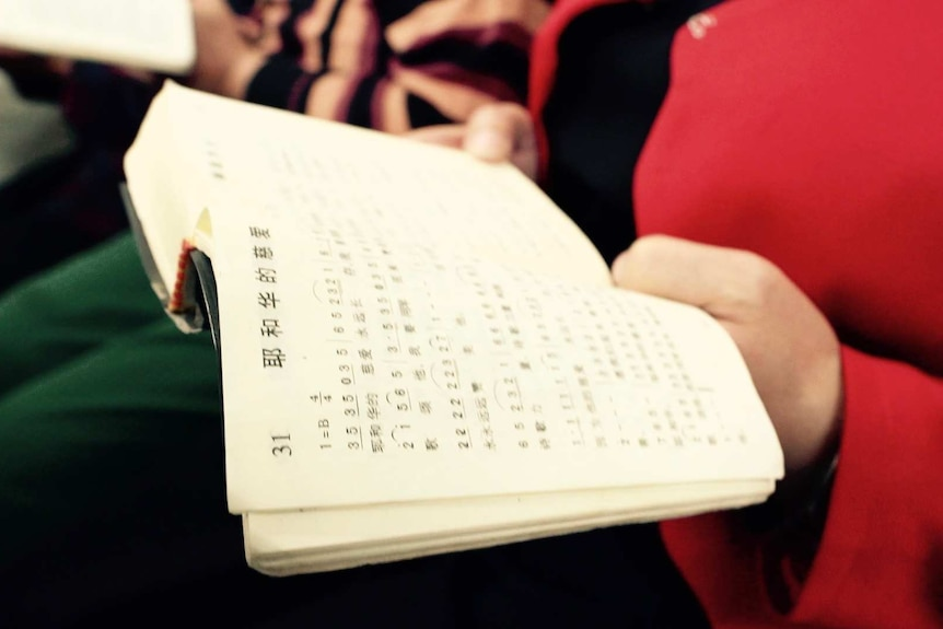 Woman holds a bible in a small underground church in Beijing